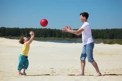 De zoon werpt bal aan vader op zand Royalty-vrije Stock Foto's