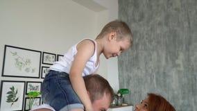 De zoon zit op schouders van de vader De familie heeft pret thuis aan het geluid van muziek stock footage
