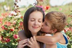 De zoons kussende moeder Stock Afbeelding