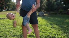 De zoonsbovenkant van de vader slingerende peuter - neer in park stock video