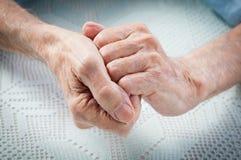 De zorg is thuis van bejaarden. Oude mensen die handen houden. royalty-vrije stock afbeelding