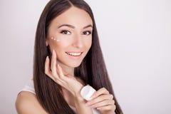 De zorg van de conceptenhuid Een jonge gezonde vrouw met kosmetische room  Stock Afbeeldingen