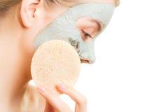 De zorg van de huid Vrouw die het gezichtsmasker van de kleimodder verwijderen Stock Foto