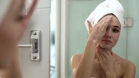 De zorg van de gezichtshuid Vrouw die Room op Huid toepassen bij Badkamers stock video