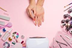 De zorg van de spijker mooie vrouwenhanden die spijkers maken die met roze zacht nagellak op een roze achtergrond worden geschild royalty-vrije stock fotografie