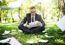 De Zorgconcept van zakenmanlooking document stress Stock Fotografie