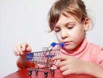 De zorgspel van het meisje met stuk speelgoed het winkelen karretje Royalty-vrije Stock Foto's