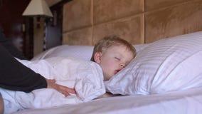 De zorgvuldige deken van moederhuiden op een slaapkind stock video