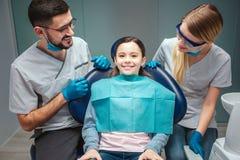 De zorgvuldige positieve mannelijke en vrouwelijke tandarts bekijkt jong geitjepatiënt en glimlach Het meisje zit als tandvoorzit stock afbeelding