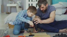 De zorgvuldige vader onderwijst zijn zoon om met elektrische schroevedraaier te werken terwijl de zoon probeert om schroefkanon t stock footage