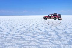 De zoute woestijn van Salar de Uyuni Bolivia - eenzame auto en stoelen royalty-vrije stock afbeeldingen