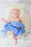De zuigeling ligt in een klein babybed verpakt blauw zacht materiaal Stock Foto's