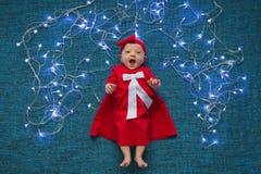 De zuigeling in rode kleding ligt op een blauwe achtergrond met Kerstmislichten stock foto