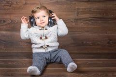 De zuigelingsjongen luistert muziek met hoofdtelefoons Stock Fotografie