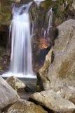 De zuivere en koude bergrivier loopt tussen rotsachtige stenen en stroomt in waterval Stock Foto