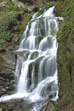 De zuivere en koude bergrivier loopt tussen rotsachtige stenen en stroomt in waterval Royalty-vrije Stock Afbeelding