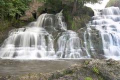 De zuivere en koude bergrivier loopt tussen rotsachtige stenen en stroomt in waterval Stock Afbeeldingen