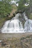 De zuivere en koude bergrivier loopt tussen rotsachtige stenen en stroomt in waterval Stock Fotografie