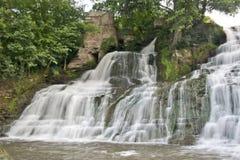 De zuivere en koude bergrivier loopt tussen rotsachtige stenen en stroomt in waterval Stock Foto's