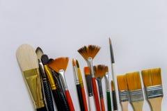 De zuivere kunst kleurde borstels met wit, zwarte en oranje varkenshaar dichte ligt omhooggaand op een wit waterverfblad De werkp royalty-vrije stock afbeeldingen