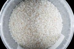 De zuivere witte rijst in een plastic emmer op een zwarte achtergrond, isoleert royalty-vrije stock afbeeldingen