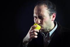 De zure zuigende mens van de citroenuitdrukking in zwarte royalty-vrije stock fotografie