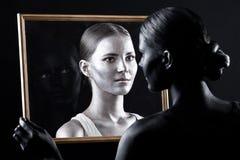 De zuster bekijkt haar tweeling door het glas Stock Afbeeldingen