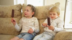 De zuster en de broer eten roomijs op stokken zittend op laag Handbediend schot stock videobeelden