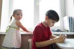 De zuster en de broer zitten in de keuken en spelen met de telefoon royalty-vrije stock afbeelding