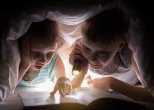 De zuster en de broer lezen een boek onder een deken met flitslicht Vrij jonge jongen en mooi meisje die pret in kinderenroo hebb stock afbeeldingen