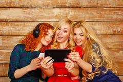De zusters die aan muziek op hoofdtelefoons luisteren en maken selfie Stock Foto