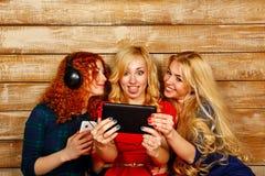 De zusters die aan muziek op hoofdtelefoons luisteren en maken selfie Royalty-vrije Stock Fotografie