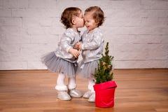 De zusters geven elkaar een kus naast een Kerstboom Royalty-vrije Stock Afbeeldingen