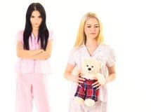 De zusters in pyjama's kijkt vijandig, jaloers Meisjes in roze pyjama's, geïsoleerde witte achtergrond Jaloersheid en afgunst stock foto