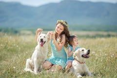 De zusters spelen met haar hond in de straat royalty-vrije stock foto