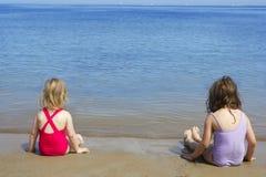 De zusters van het slepen zitten op het zwempak van het strandbadpak Stock Afbeeldingen
