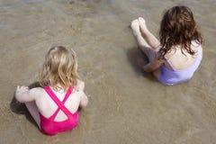 De zusters van het slepen zitten op het zwempak van het strandbadpak Stock Fotografie