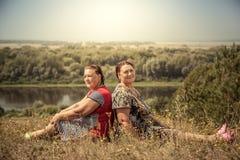 De zusters van paar het hogere vrouwen rusten samen rijtjes in platteland in zonnige de zomerdag stock fotografie