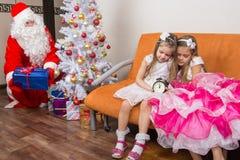 De zusters vielen in slaap terwijl het wachten op Santa Claus, die stil voorstellen onder de Kerstboom zetten Stock Foto