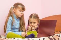 De zusters zijn geinteresseerd in het letten van het op laptop scherm stock foto's
