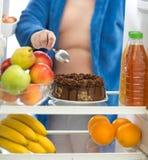 De zwaarlijvige kerel verkiest chocoladecake van koelkast dan fruit stock foto's