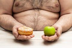 De zwaarlijvige mens houdt in handen een appel en een doughnutconcept een taaie keus tussen tegenovergesteld alternatieven gezond stock foto's