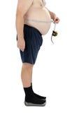 De zwaarlijvige mens meet zijn taille op schalen Stock Foto