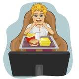 De zwaarlijvige vette jongen zit als voorzitter die hamburger eten en op TV letten Royalty-vrije Stock Afbeeldingen