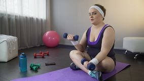 De zwaarlijvige vrouw die gemakkelijk spieren met domoren opbouwen, wil gewicht verliezen stock video