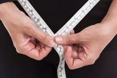 De zwaarlijvige vrouw meet haar taille door band, gezondheidszorg te meten Royalty-vrije Stock Afbeeldingen