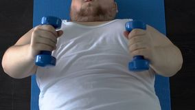 De zwakke opheffende domoren van de spieren vette mens omhoog met inspanning die op vloer, geschiktheid liggen stock video