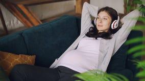 De zwangere jonge dame luistert aan muziek met draadloze hoofdtelefoons die op laag in woonkamer thuis rusten Mooi stock video