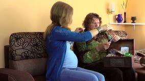 De zwangere kleindochter met hogere grootmoeder neemt juwelen stock videobeelden