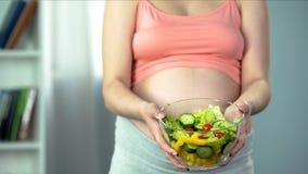 De zwangere kom van de vrouwenholding van plantaardige saladerijken in vitaminen en voedingsmiddelen royalty-vrije stock foto's
